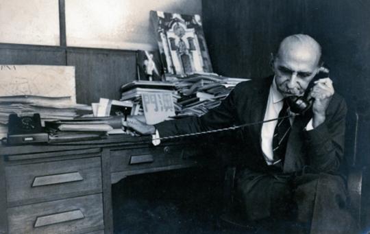 Paolo Gasparini: O Chefe da Divisão de Estudos e Tombamentos, o Arquiteto Lúcio Costa,  na repartição do IPHAN com fotografias sobre a mesa de trabalho, s/d.